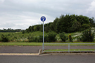 'Untitled, 2014' from the project 'The Fall and Rise of Ravenscraig' by photographer Colin McPherson.<br /> <br /> The photograph shows a signpost and pavement outside the Ravenscraig Regional Sports Facility, build in 2010 on the site of the former steelworks at Ravenscraig.<br /> <br /> This project, photographed in 2014, looks at the topography of the post-industrial landscape at Ravenscraig, the site until its closure in 1992 of the largest hot strip steel mill in western Europe. In its current state, Ravenscraig is one of the largest derelict sites in Europe measuring over 1,125 acres (4.55 km2) in size, an area equivalent to 700 football pitches or twice the size of Monaco. It is currently being developed with a mix of housing, retail and the home of South Lanarkshire College and the Ravenscraig Regional Sports Facility.