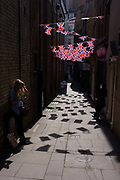 Lone woman beneath British Union Jack flags strung together across a London alleyway, near Bond Street.
