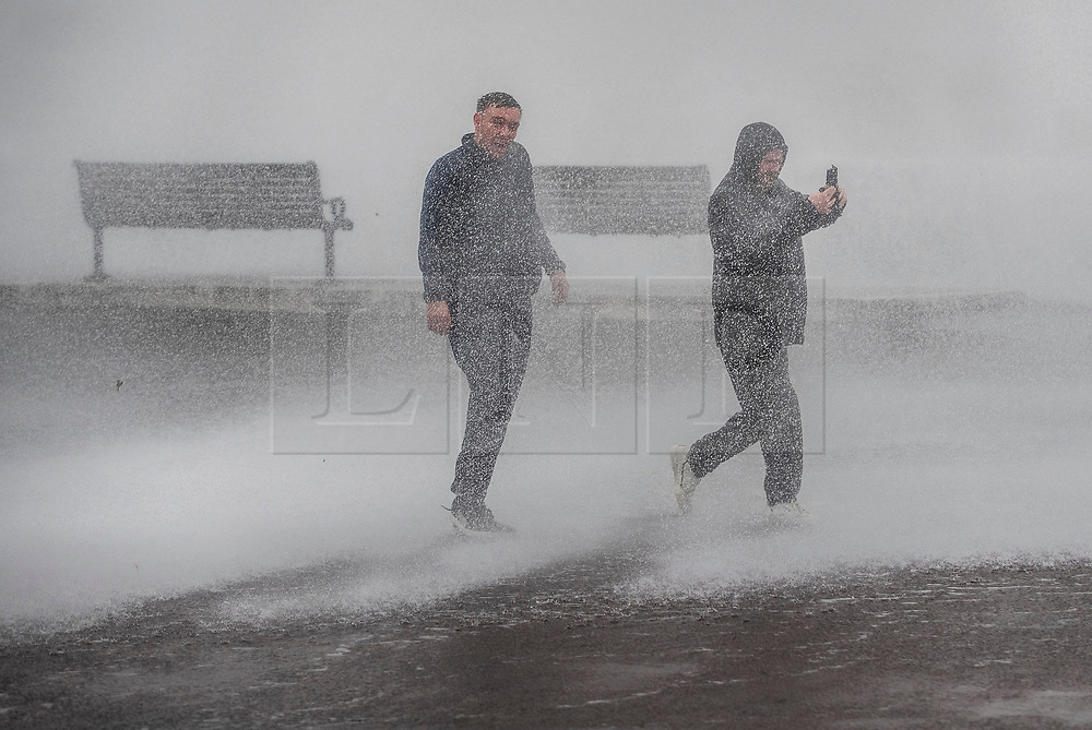 © Licensed to London News Pictures. 09/02/2020. Portsmouth, UK. A man films his friend as they get a soaking from the waves during high tide at Southsea, Portsmouth as Storm Ciara batters the UK. Airlines have cancelled dozens of domestic and international flights as the storm brings strong winds and rain. Photo credit: Peter Macdiarmid/LNP