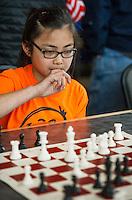 Catherine Pignol from Holy Trinity School thinks through her next move in her match with Dylan Dickey from Laconia Middle School during the  Laconia City Wide Chess Tournament at the Huot Center Saturday morning.  (Karen Bobotas/for the Laconia Daily Sun)