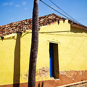 A house and powerline on a cobblestone street in Trinidad, Cuba.