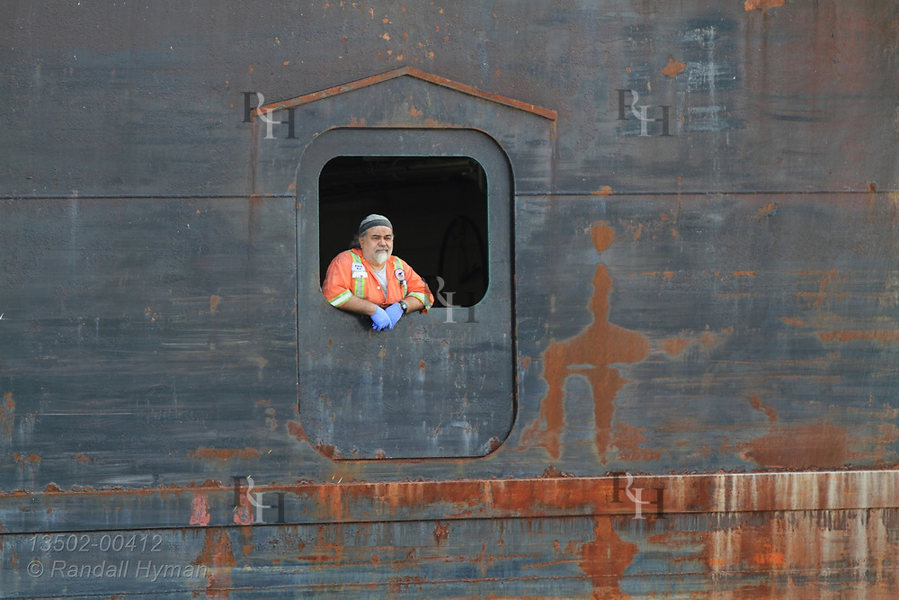 Deckhand gazes from opening in side of freighter as it exits harbor on Lake Erie at Lorain, OH.