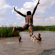 At the outskirts of an informal settlement in Limpopo, South Africa, a youngster is skinny dipping into a nearby water hole that is recently completely filled due to heavy rainfall. November 26th 2014<br /> <br /> Born Frees', as the South African people call the new generation of South Africa. It's the first generation born after the ending of the Apartheid in South Africa in 1994. These children didn't experience the oppression, segregation and the horrors of war, but are most vulnerable to the issues of a rapidly changing lifestyle. (De Beeldunie/ Frank Trimbos)