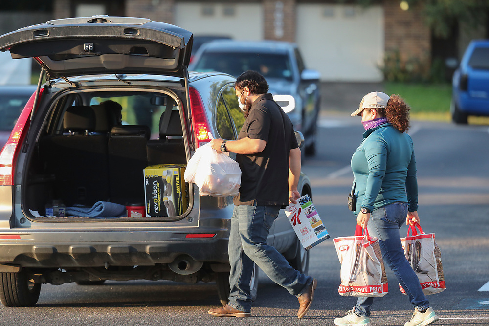Staff members including Alejandro DelValle (l) and Arlene Lozano help conduct a twice-weekly fresh food drive sponsored by Catholic Charities helping low-income Texans  make ends meet in Austin. The October 1, 2020 effort helped several hundred family members with fruit, meats, milk and cereal.