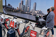 Pedestrians pass-by Santander-sponsored rental bikes awaiting riders and lined up in their charging docks in front of a construction hoarding that shows the Southbank skyline, on 22nd June 2021, in London, England.