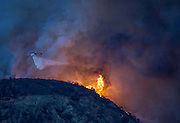 A helicopter drops water during a brushfire in San Gabriel Canyon above Azusa, California, Monday, September 23, 2013.  A fire that began above Azusa burned north into the Angeles National Forest and was growing. The fire started at 5:56 p.m. and county firefighters fought the blaze with SuperScoopers, helicopters and ground forces. (Photo by Ringo Chiu/PHOTOFORMULA.com)