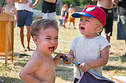 Two young boys crying with anger over possession of a toy in a picnic, 19th July 2015, Lagrasse France.
