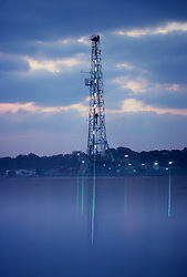 Stock photo of an oil and gas drilling rig on a foggy morning in Texas
