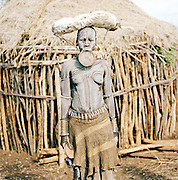 Mursi tribal woman by a hut with goat skin water carrier on her head in Omo Valley, Southern Ethiopia. The Mursi consider the lip plate as a form of beauty.