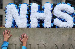 © Licensed to London News Pictures. 09/01/2016. London, UK. A child of a health worker reaches up to a floral tribute in the shape of an NHS logo during a rally against the proposed cancellation of bursaries for nurses hoping to train for work in the NHS.  Photo credit: Peter Macdiarmid/LNP