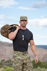 muscular solider with a bag over his shoulder outdoors