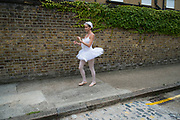 Ballet dancer from the Ruggieri Dance Academy practices her positions in an unexpected urban environment prior to a performance at a local Summer event in Wapping, London, England, United Kingdom.