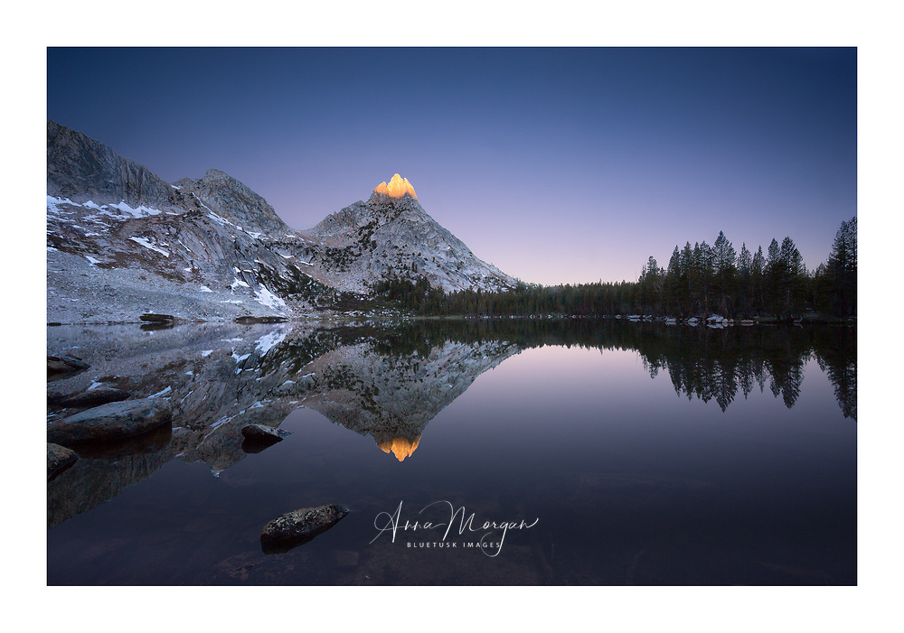 A peep of morning sun on top of Ragged Peak reflected in a still and simple composition at Lower Young Lake, Yosemite Wilderness, California