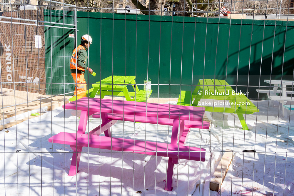 A construction contractor paints benches green and pink, located at Elephant Park in south London, on 29th March 2021, in London, England.