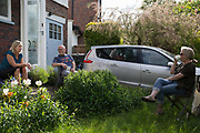 As the country continues the UK governments Coronavirus lockdown with social distancing rules still in effect, a middle-class couple chat 2 metres apart with a neighbour in the front garden outside their home in Herne Hill, south London, on 17th May 2020, in London, England.
