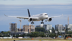 July 2, 2018 - Richmond, British Columbia, Canada - A Lufthansa Airbus A350-900 (D-AIXK) extra wide body jet airliner, painted in the airline's new-look livery, airborne on final approach for landing at Vancouver International Airport, passes by new high-rise condominium construction in Richmond, British Columbia, Canada. (Credit Image: © Bayne Stanley via ZUMA Wire)