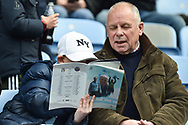 A Young boy reads his match day programme while his granddad looks on during the EFL Sky Bet League 1 match between Coventry City and Shrewsbury Town at the Ricoh Arena, Coventry, England on 28 April 2019.