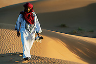 Traditional dressed Moroccan man with red turban in the Sahara desert.