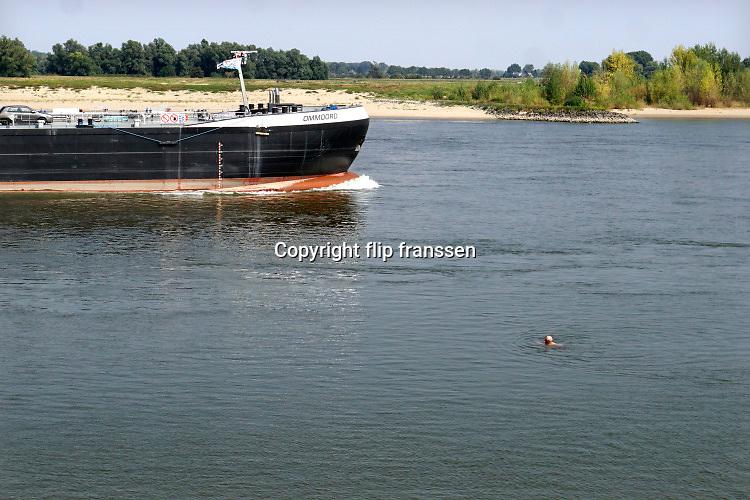 Nederland, Ooijpolder, 12-8-2020 Mensen zoeken verkoeling langs het water op deze tropische dag. Langs de rivieren zoals hier aan de Waal, rijn, zijn veel rivierstrandjes waar mensen gebruik van maken.  Een oudere man zwemt in de rivier terwijl een binnenvaartschip langs komt . Zwemmen in de waal en rijn is gevaarlijk en verboden . Foto: ANP/ Hollandse Hoogte/ Flip Franssen