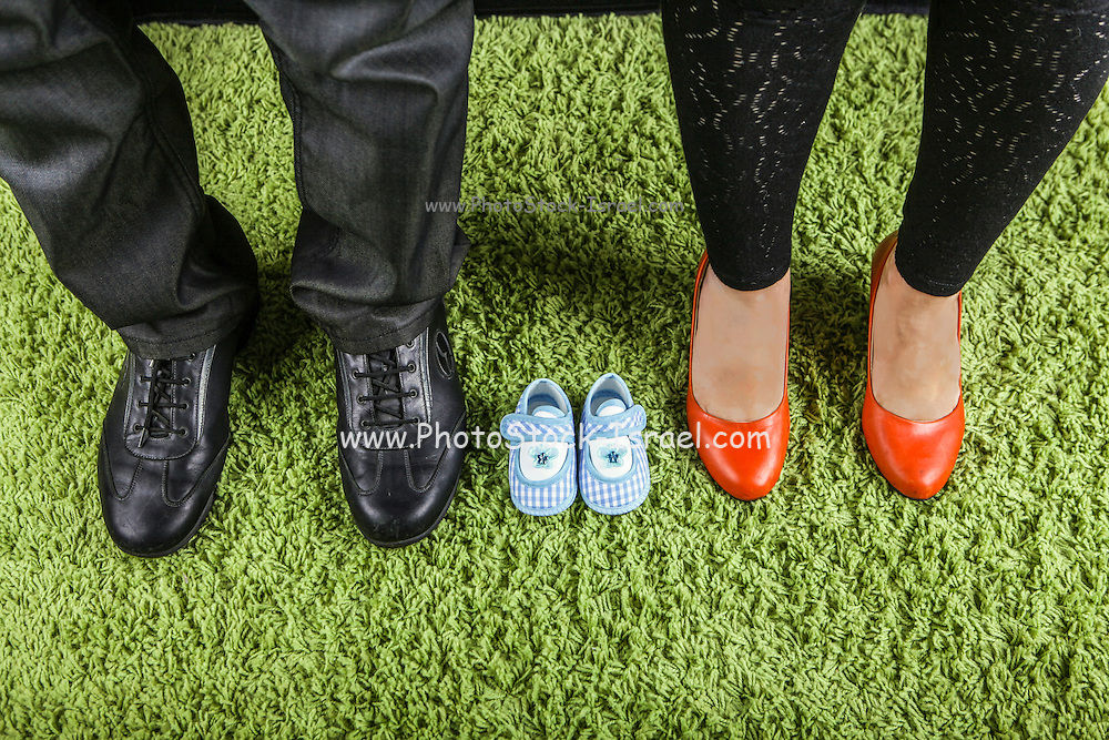 Expecting Couple concept feet of mother and father with baby shoes on green Carpet