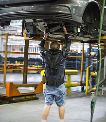 """January 2, 2018 - inconnu - Car giant Ford is to provide assembly line workers with powered exoskeletons to make their work easier.The EksoVest will provide the user with between 2.26 kilos and 6.8 kilos / 5lbs and15lbs of lift assistance, ideal for any action required under the vehicle. Some of these activities might include pushing in fastener rivets, snapping fuel lines into place or simply using any drill or impact drivers or torque wrenches.The vests , made of carbon fibre and steel tubing, are being supplied by US company Ekso Bionics in a pioneering partnership with Ford.A spokesman for Ekso Bionics said:"""" The physical demands of repetitive overhead work takes its toll on workers. """"Some workers on the assembly line lift their arms an average of 4,600 times per day, or about 1 million times per year, increasing the possibility of fatigue or injury.""""That's where the EksoVest comes in. """"Ford and Ekso Bionics partnered to explore how the upper body exoskeleton that elevates and supports a worker's arms can help.By reducing the strain on a worker's body, they feel better at the end of every day, the likelihood of sustaining injury is reduced.Jobs get completed to a higher level of quality, in a shorter amount of time, increasing both productivity and morale.Ford tested the EksoVest in two U.S. plants. As a result, use of the EksoVest will be expanded to plants in other regions, including Europe and South America.Ekso Bionics is headquartered in a former ford factory in California which opened in 1931 and was the largest auto assembly plant on the West Coast. Ekso Bionics co-founder Russ Angold said:"""" Collaboratively working with Ford enabled us to test and refine early prototypes of the EksoVest based on insights directly from their production line workers. """"The end result is a wearable tool that reduces the strain on a worker's body, reducing the likelihood of injury, and helping them feel better at"""