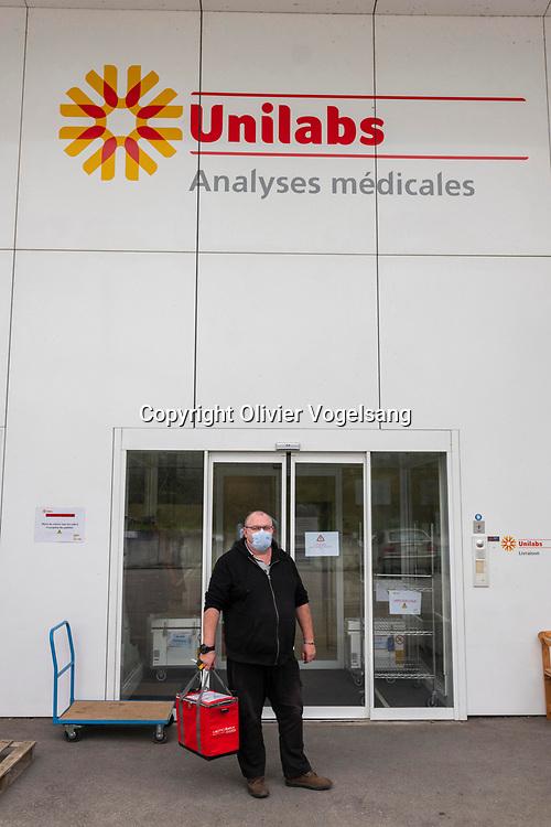 Coppet, 30 mars 2020. Dans les laboratoires d'analyse privés d'Unilabs  à Coppet. On se prépare à faire des tests sérologiques de dépistage du Covid-19. Un coursier apportent des analyses au labo. © Olivier Vogelsang