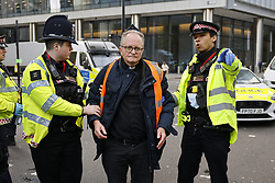 © Licensed to London News Pictures. 25/10/2021. London, UK. Police detain Insulate Britain activist Vicar Mark Coleman after he glued himself to the road at Bishopsgate in the City of London. The group have restarted their actions to block motorways and major roads causing disruption in the week before the COP26 climate meeting in Glasgow on 31/10/2021. Photo credit: Peter Macdiarmid/LNP