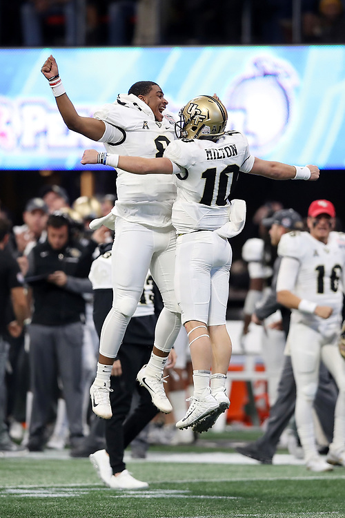 UCF Knights quarterback McKenzie Milton (10) celebrates a touchdown with quarterback Darriel Mack Jr. (8) during the 2018 Chick-fil-A Peach Bowl NCAA football game against the Auburn Tigers on Monday, January 1, 2018 in Atlanta. (Jason Parkhurst / Abell Images for the Chick-fil-A Peach Bowl)