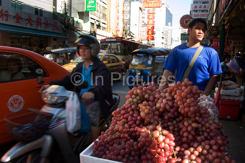 Grape seller. Bangkok's bustling Chinatown (Sampeng) has an almost more authentic old China atmosphere and visual appearance than much of China itself. A compact area of shops Chinese signage, market stalls, food, transport workers and crowds, this area is in distinct contrast to Thai areas. Alleyways, narrow streets all fit together and are lined by shop-houses.
