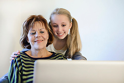 Grandmother and granddaughter using laptop, smiling