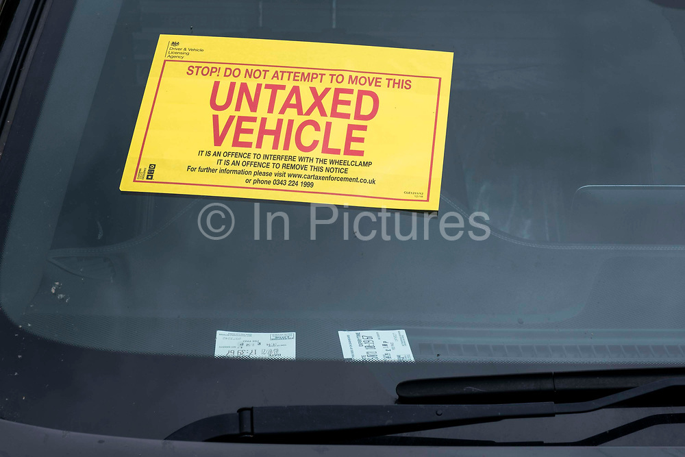 A bright yellow DVLA sign informing a driver of the wheel clamp on their vehicle in a side street on the 15th of July 2021 in Folkestone, United Kingdom. The DVLA use automatic number plate readers to locate untaxed vehicles on the streets and clamps them until tax and fines have been paid. A clamped vehicle cannot be moved until it is removed.