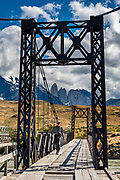 The old bridge crossing Rio Paine frames the namesake towers of Torres del Paine National Park, near Laguna Amarga Entrance and Range Station, in Ultima Esperanza Province, Chile, Patagonia, South America. The Park is listed as a World Biosphere Reserve by UNESCO.