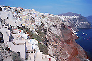 Oia village perches on volcanic cliffs which rise steeply above Armeni Bay, on Santorini Island, Greece, Europe. Geologic and human history of Santorini: Humans first arrived around 3000 BC on this volcano known in ancient times as Thira (or Thera). The island was a volcanic cone with a circular shoreline until 1646 BC, when one of earths most violent explosions blasted ash all over the Mediterranean, sunk the center of the island, launched tidal waves, and may have ruined the Minoan civilization 70 miles away on Crete. Remarkably, volcanic ash dumped onto the volcanos flanks actually preserved the village of Akrotiri and its 3600-year-old frescoes from the Minoan era. These are some of the earliest known examples of world art history, which you can now view in museums. In 286 BC, the volcano split off Thirasia (Little Thira) Island (to the West). The volcano began rebuilding, and in 197 BC the small center islet of Palia Kameni appeared. In 1707 CE, lava started forming Nea Kameni, the larger center island which erupted as recently as 1956 and caused a huge earthquake (7.8 on the Richter scale) which destroyed most of the houses in the towns of Fira and Oia. Fira and Oia have since been rebuilt as multi-level mazes of fascinating whitewashed architecture, attracting tourists from around the world.