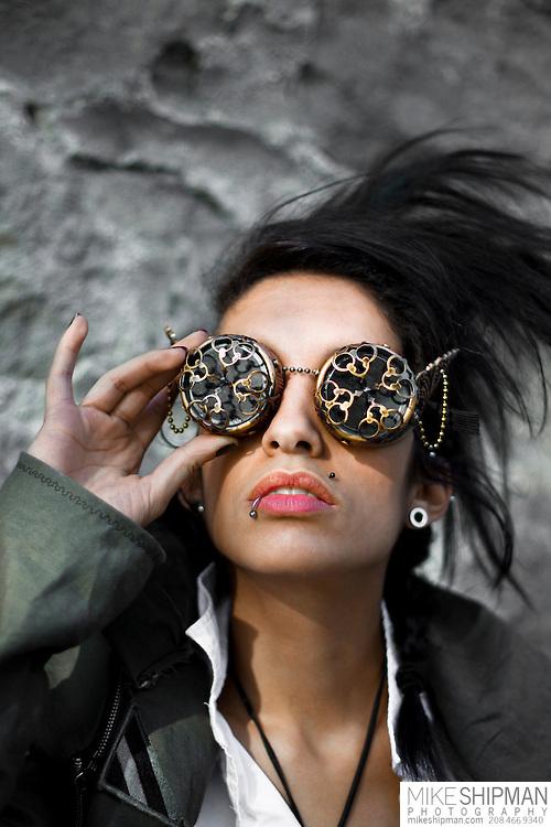 Brunette woman wearing bronze steampunk goggles and spikey hair, headshot