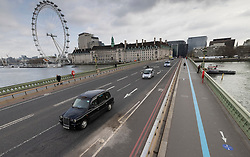 © Licensed to London News Pictures. 24/03/2021. London, UK. Light traffic on Westminster Bridge on the anniversary of the announcement of the first lockdown on March 24th 2020. Traffic is still relatively light, but the pavements are marked with a blue line one way system for pedestrians to enable social distancing. Coronavirus restrictions are to be eased over the coming weeks as vaccinations near 30 million and infection rates and deaths continue to drop. Photo credit: Peter Macdiarmid/LNP