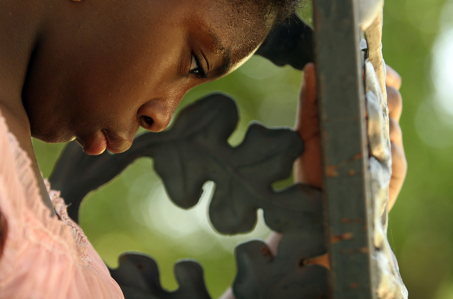 Tia's sister, Precious Wright, is lost in thought as she hangs out on their front porch while her mother is at work.