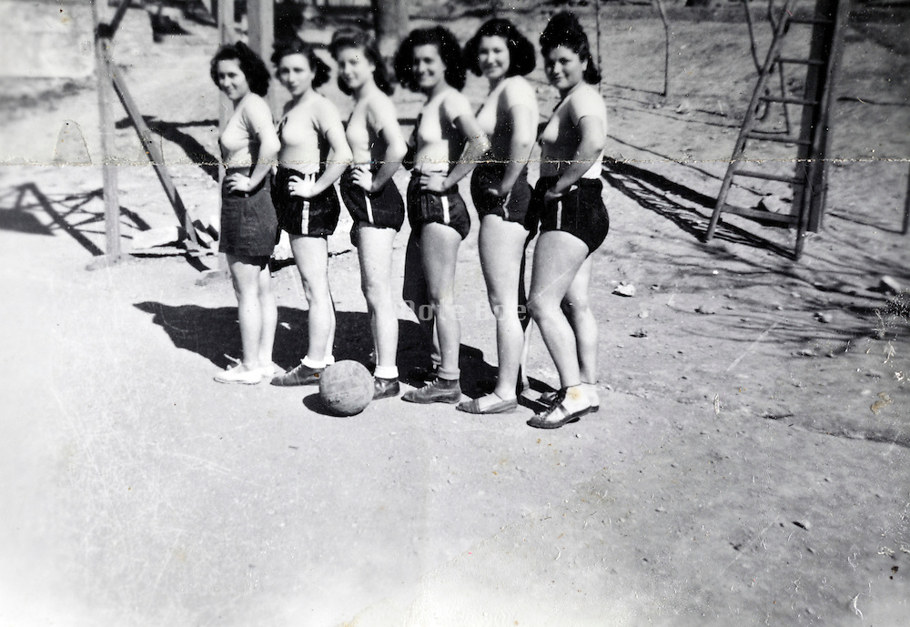 all girls team posing with a football