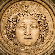 Medallion decorated with Medusa's head on display in the main building of the Istanbul Archaeology Museums. The depiction is unusual in several respects. Rather than facing straight ahead, the head to turned slightly to the left, with the eyes looking in the same direction. She does not look menacing, but rather smiling in surprise. And sankes that should have formed her hair are represented with their tails knotted under and her chin and their heads raised above her forehead. The Istanbul Archaeology Museums, housed in three buildings in what was originally the gardens of the Topkapi Palace in Istanbul, Turkey, holds over 1 million artifacts relating to Islamic art, historical archeology of the Middle East and Europe (as well as Turkey), and a building devoted to the ancient orient.