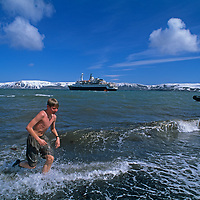 Nick Wiltsie (MR) runs out of icy polar seas after soaking in hot spring on Deception Island, Antarctica.  The cruise ship Clipper Adventurer is anchored in the background.
