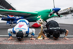Yoshihide Muroya of Japan kisses the yard of bricks with 2017 Indy 500 winner and former Formula 1 driver Takuma Sato of Japan after he won at the eighth round of the Red Bull Air Race World Championship at Indianapolis Motor Speedway, United States on October 15, 2017. // Joerg Mitter / Red Bull Content Pool // P-20171016-00111 // Usage for editorial use only // Please go to www.redbullcontentpool.com for further information. //