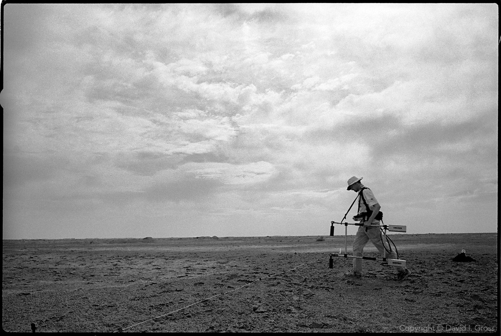 """A member of Inforce, a UK team of """"grave hunters"""", scan the soil for disturbance to check for the presence of a mass grave, near Al-Musayab, Iraq. This was the first time the ensemble of high-tech geological tools had been employed to look for a mass grave."""