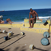 Fitness enthusiasts work out at an outdoor gymnasium overlooking the ocean at Parque do Arpoador, between the beaches of Ipanema and Copacabana, Rio de Janeiro,  Brazil. 6th July 2010. Photo Tim Clayton..The beaches of Rio de Janeiro, provide the ultimate playground for locals and tourists alike. Beach activity is in abundance as beach volley ball, football and a hybrid of the two, foot volley, are played day and night along the length and breadth of Rio's beaches. .Volleyball nets and football posts stretch along the cities coastline and are a hive of activity particularly at it's most famous beaches Copacabana and Ipanema. .The warm waters of the Atlantic Ocean provide the ideal conditions for a variety of water sports. Walkways along the edge of the beaches along with exercise stations and cycleways encourage sporting activity, even an outdoor gym is available at the Parque Do Arpoador overlooking the ocean. .On Sunday's the main roads along the beaches of Copacabana, Leblon and Ipanema are closed to traffic bringing out thousands of people of all ages to walk, run, jog, ride, skateboard and cycle more than 10 km of beachside roadway. .This sports mad city is about to become a worldwide sporting focus as they play host to the world's biggest sporting events with Brazil hosting the next Fifa World Cup in 2014 and Rio de Janeiro hosting the Olympic Games in 2016..