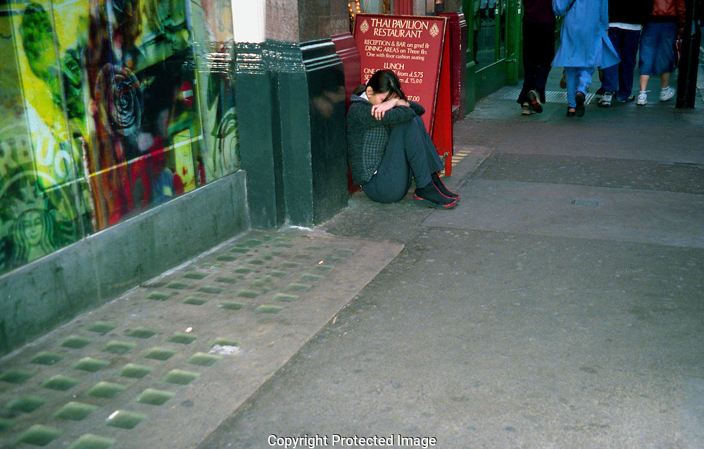 Young homeless girl alone and miserable at night in streets of London.