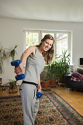Young woman doing exercise with dumbbell in living room and smiling, Munich, Bavaria, Germany