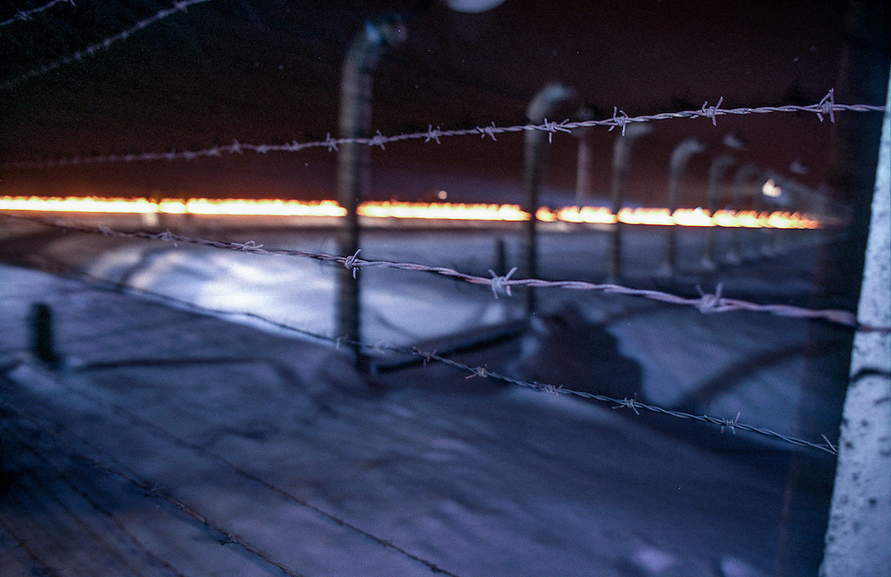 A barbed wire fence surrounds the Auschwitz (Birkenau) Nazi concentration camp with a symbolic fire on the former railway track during the 60th anniversary ceremony of the liberation on the 27th of January 1995. It is estimated that between 1.1 and 1.5 million Jews, Poles, Roma and others were killed here in the Holocaust between 1940-1945.