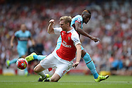 Per Mertesacker, the Arsenal captain is tackled by Diafra Sakho of West Ham United. Barclays Premier League, Arsenal v West Ham Utd at the Emirates Stadium in London on Sunday 9th August 2015.<br /> pic by John Patrick Fletcher, Andrew Orchard sports photography.