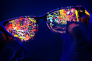 A microfiber cloth is used to clean glowing paint off of a pair of glasses. Blacklight photography.