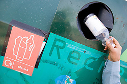Man recycling a plastic bottle,