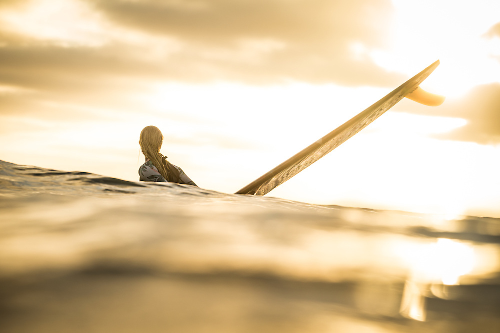 Surfer girl sitting on her longboard in golden light, waiting for a wave in Mission Beach, San Diego, CA.