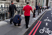 A businessman stops to tie a loose shoelace on Lombard Street in the City of London, (aka The Square Mile) the capital's financial district, on 3rd September 2019, in London, England.